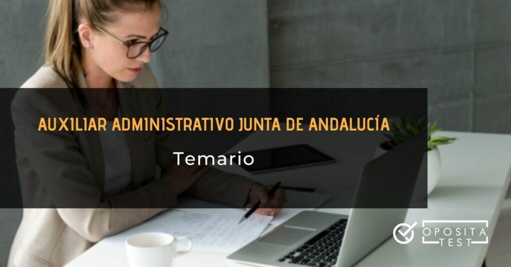 Mujer rubia de traje blanco ante ordenador portátil y papeles con printer para acompañar la temática temario de la oposición a auxiliar administrativo de la Junta de Andalucía