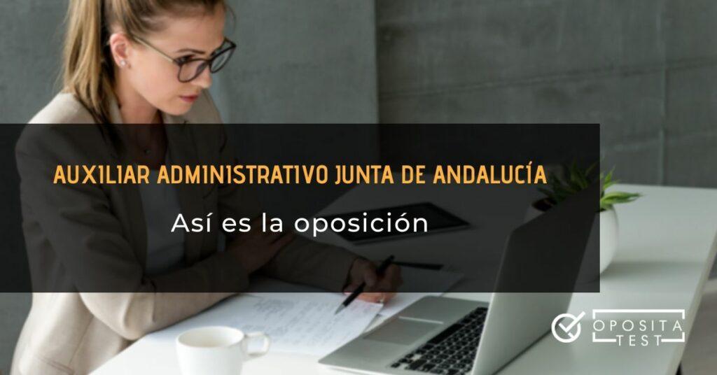 Mujer rubia con pelo recogido y gafas trabajando en ordenador con hojas de papel para ilustrar el concepto de oposición a auxiliar administrativo de la Junta de Andalucia