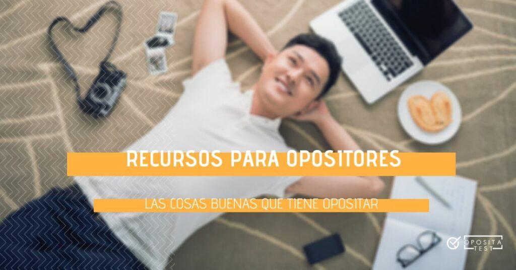 Imagen de persona en camiseta blanca y vaqueros tumbada sobre la alfombra con ordenador portátil, libreta y cámara de fotos para ilustrar las cosas buenas que tiene opositar