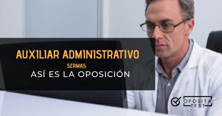 Auxiliar administrativo sentado frente a una pantalla de ordenador detrás del mostrador. Toda la imagen está fuera de foco. Se utiliza para ilustrar una entrada sobre la oposición de Auxiliar Administrativo del SERMAS.